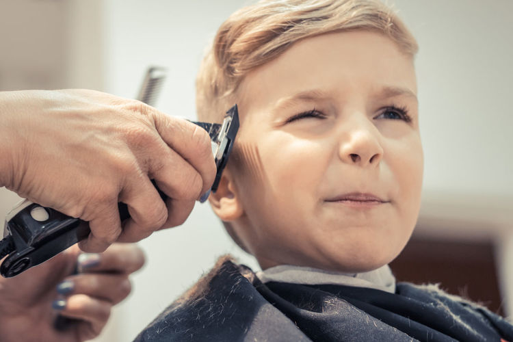 Cropped hands of female hairdresser styling boy hair in salon