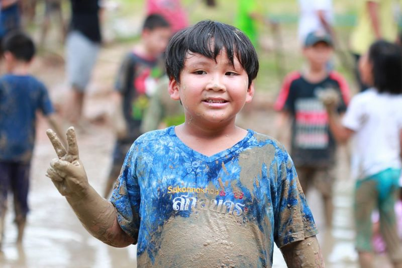 Cute boy covered in mud while gesturing peace sign outdoors