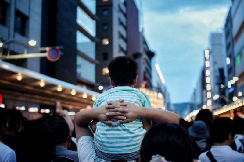 Rear View Of Father Carrying Son On Shoulder At Gion Festival