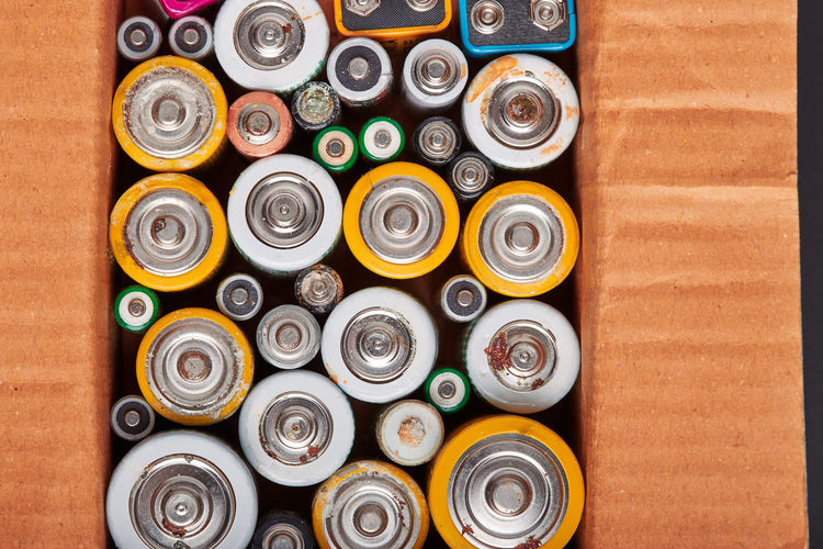 Discharged batteries in cardboard box. collecting used batteries to recycle