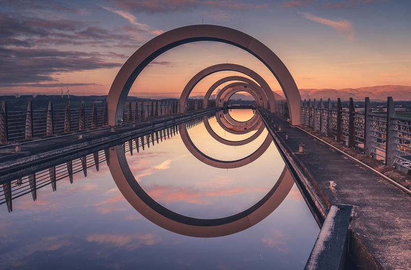 Reflection of railing in water against sky during sunset