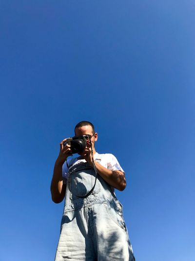 Poloroid Camera Overall Dungerees Sky Low Angle View One Person Blue Copy Space Lifestyles Clear Sky Men Standing Real People Young Men Camera - Photographic Equipment Outdoors Sunlight Day Photography Themes Nature