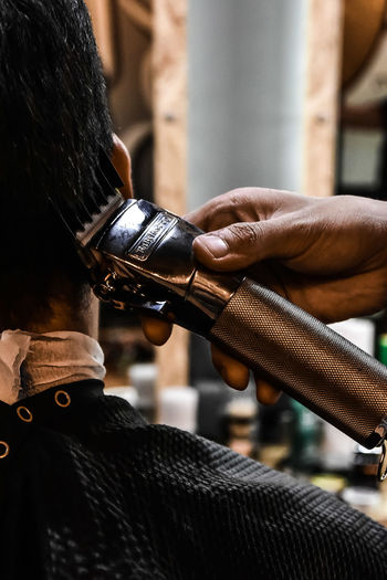 Cropped hand of barber cutting male customer hair in shop