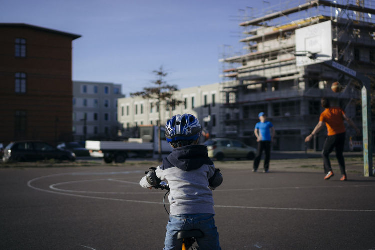 Rear View Of Boy On Bicycle Looking At Men Playing Basketball