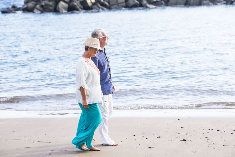 Side View Of Senior Couple Walking At Beach