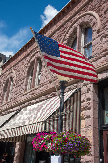 Sep - 2018 American Flag Blowing In The Wind Architecture Building Building Exterior Built Structure Day Flag Flower Flowering Plant Low Angle View Nature No People Patriotism Plant Sky Stone Structure Striped Window