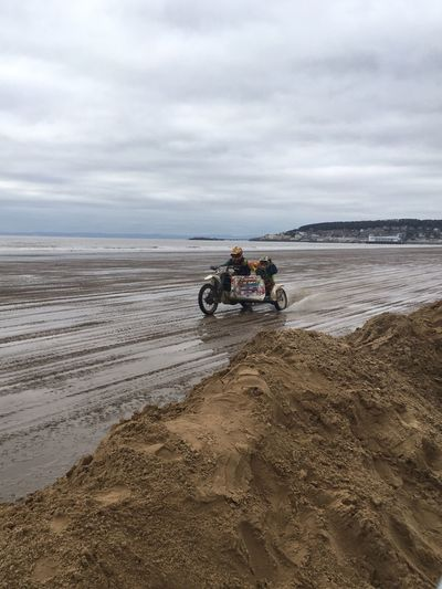 Man with friend riding motorcycle on beach against sky