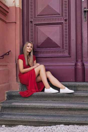 Woman sitting on steps against closed doors