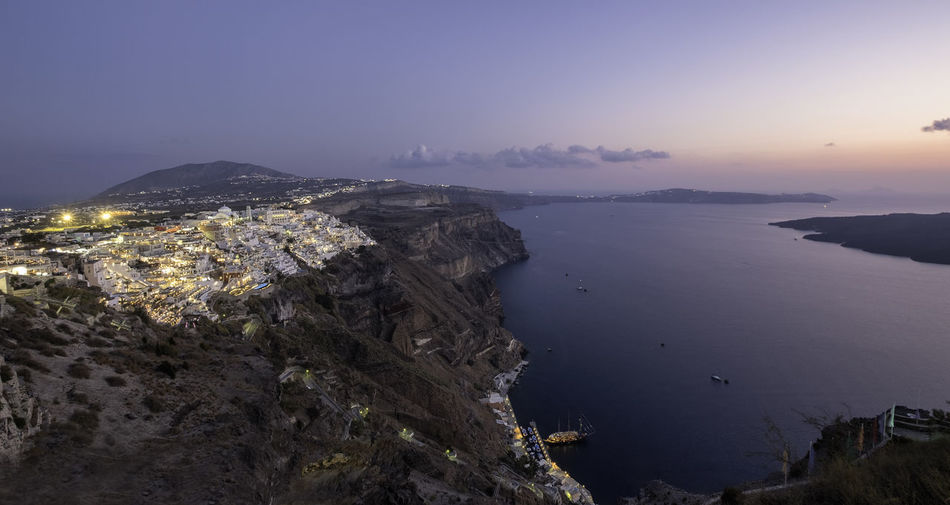 Rocky mountain by sea against sky during sunset in fira