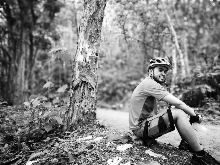 Cyclist looking away while sitting by trees