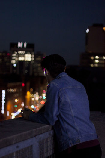 Rear view of man standing on terrace in city at night