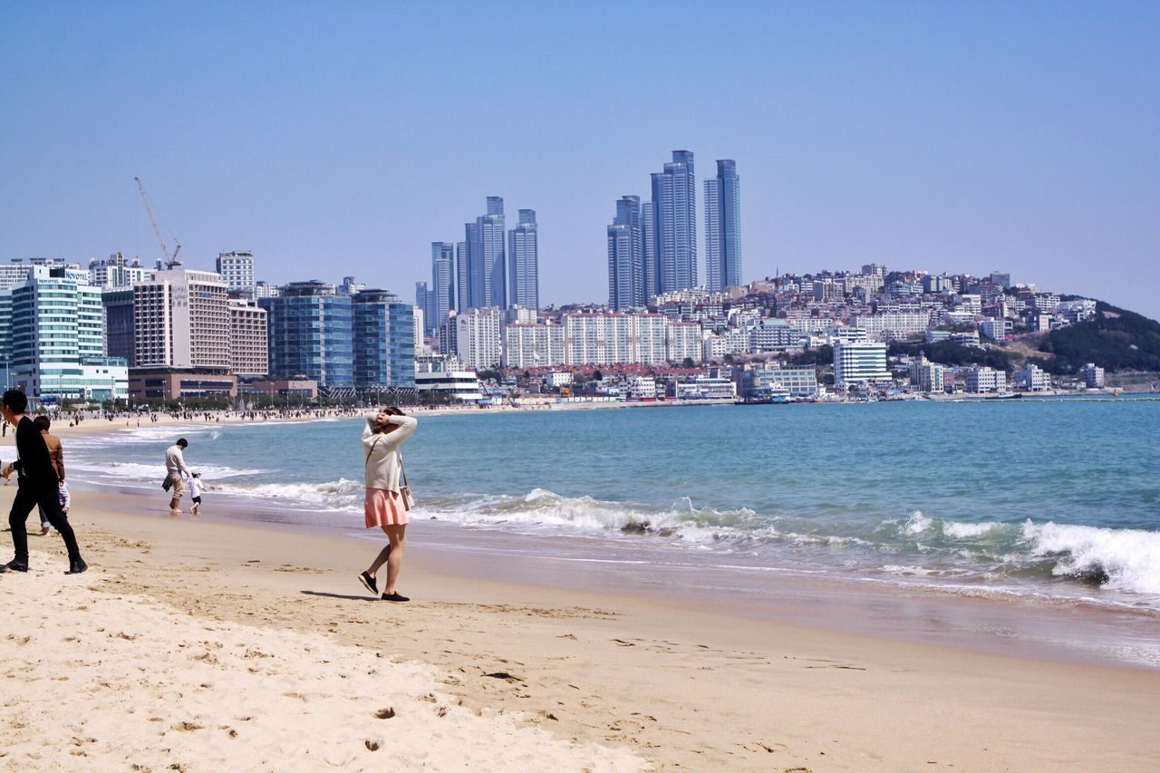 beach, sea, shore, real people, architecture, sand, building exterior, skyscraper, built structure, clear sky, full length, water, wave, leisure activity, city, lifestyles, sky, cityscape, vacations, day, outdoors, men, nature, urban skyline, modern, beauty in nature