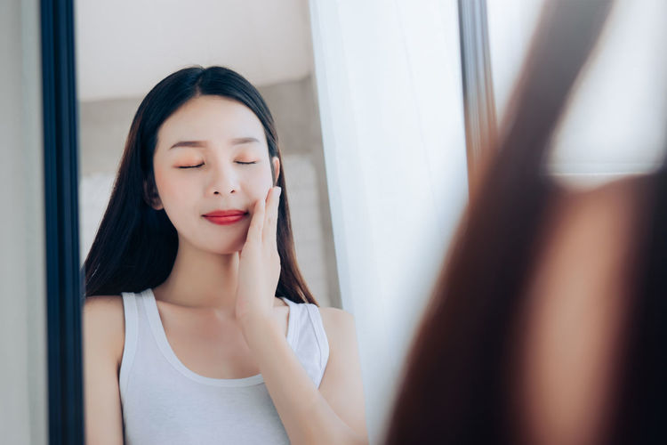 Young Beauty Asian Woman Looking at Mirror Check Clear Face Skincare and Smile Morning in White Bedroom. One Person Young Adult Adult Women Indoors  Beauty Hair Beautiful Woman Young Women Hairstyle Reflection Headshot Mirror Make-up Front View Portrait Looking Long Hair Lipstick Contemplation