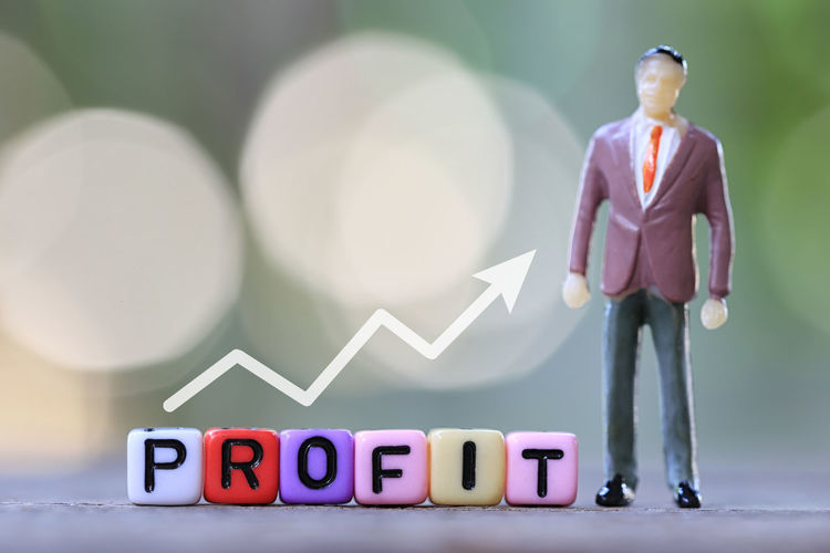 Businessman stand near textbox of Profit and green blur bokeh background in concept of growth in business. Green Color Standing Adult Business Business Person Businessman Businessman Day Capital Letter Communication Figurine  Focus On Foreground Full Length Human Representation Male Likeness Males  Men Nature One Person Profit Profit Motive Representation Text Text Box Toy Western Script