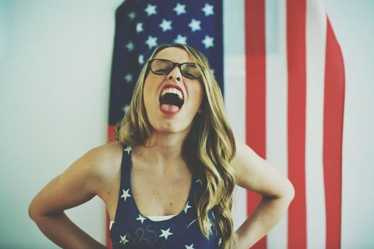 Portrait of woman with mouth open against american flag