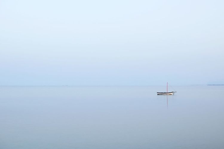 Boat sailing on sea against sky during foggy weather