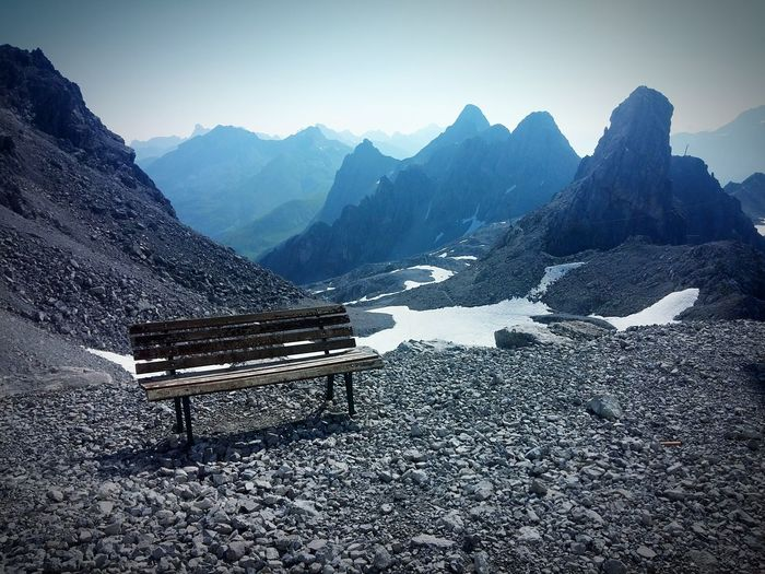 Empty bench against mountains