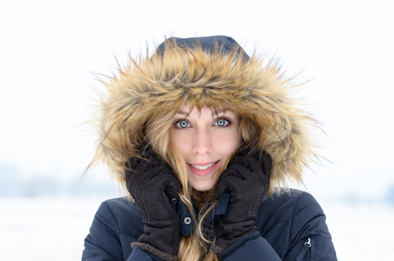 looking at camera, portrait, real people, lifestyles, warm clothing, cold temperature, front view, one person, winter, leisure activity, smiling, focus on foreground, happiness, young adult, young women, headshot, day, outdoors, snow, blond hair, nature, beautiful woman, close-up, sky