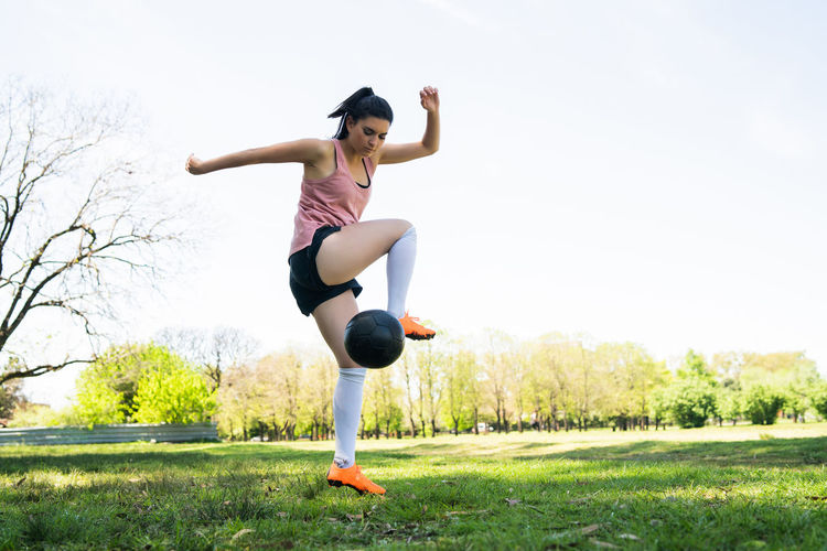 Full length of woman jumping on field against sky