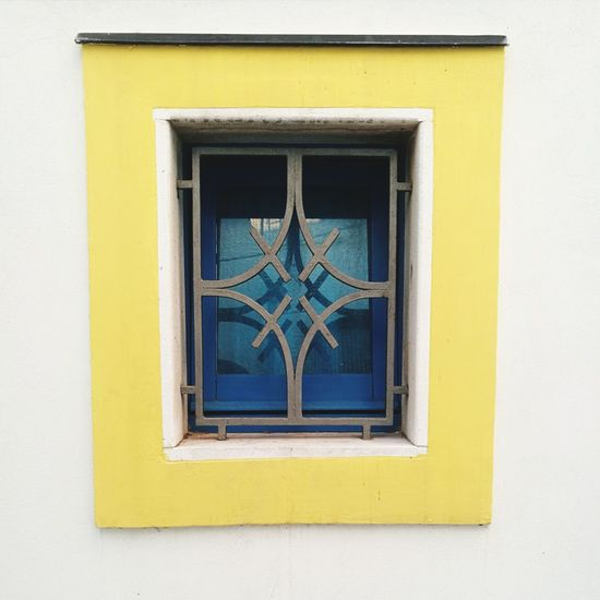 Closed window on white wall of building