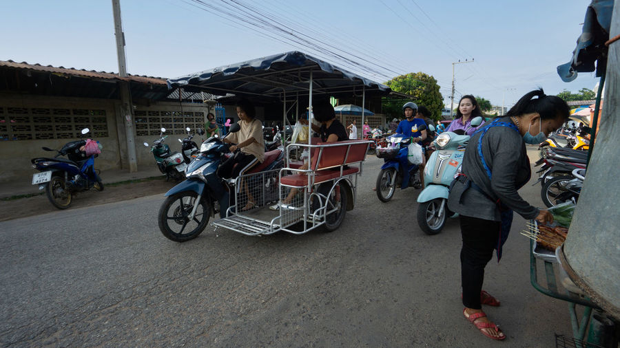 People riding motorcycle on road in city