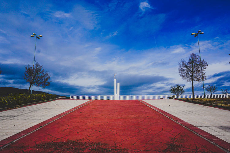 Footpath by sea against blue sky