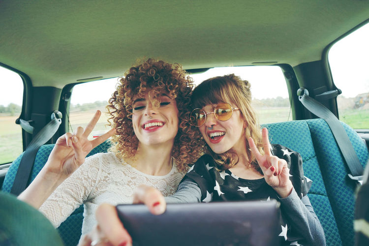 Cheerful Female Friends Taking Selfie While Sitting In Car
