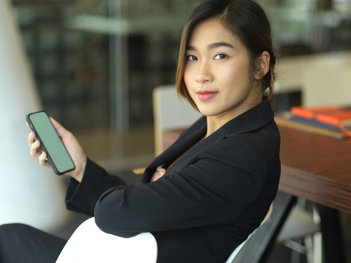 Portrait of young businesswoman holding mobile phone in office