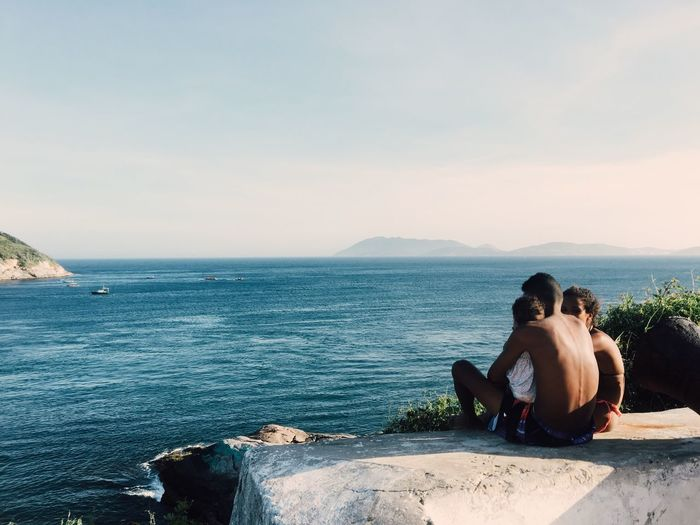 Rear view of couple sitting on sea against sky