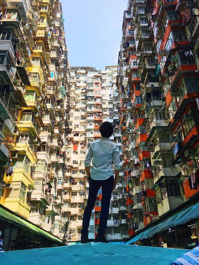 Rear view of man standing buildings in city