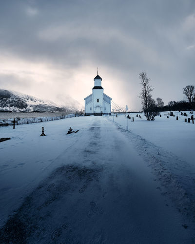 Snow covered cemetery against cloudy sky