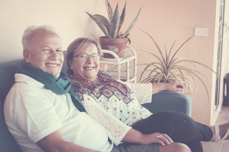 Cheerful senior couple sitting on sofa at home