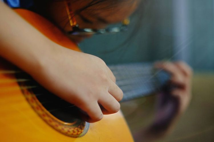 Asian girls wearing eyeglasses is practicing guitar to be able to play her favorite song. Jass Song Meditation Happyness Background Lifestyle Acting Action Casual Comfortable Concert Cozy Cultivate Culture Effort Emotion Entertainment Melody Musis Rhythm Show Solo Voice Tercet Private World Close-up