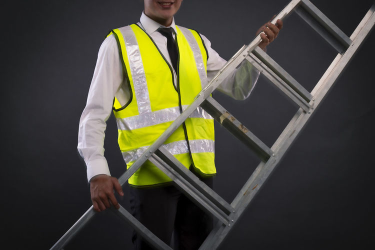 Midsection of construction worker holding ladder while standing against gray background