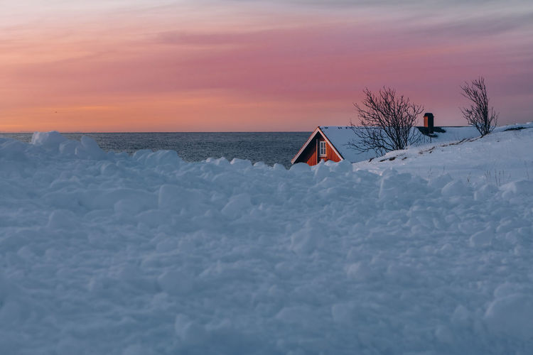 Snow covered land and sea against sky during sunset