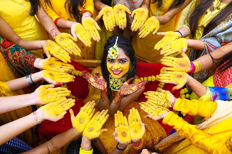 Portrait of smiling bride amidst women during haldi ceremony