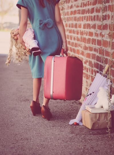 Low section of girl carrying doll and briefcase by brick wall