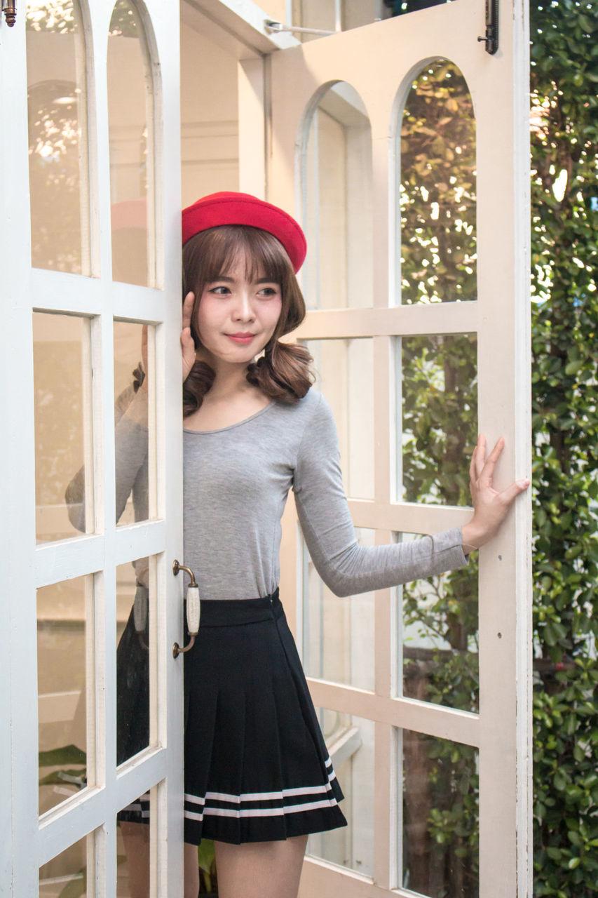 Mid Adult Woman Standing In Doorway