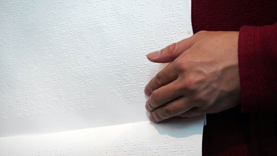 Cropped image of woman touching braille