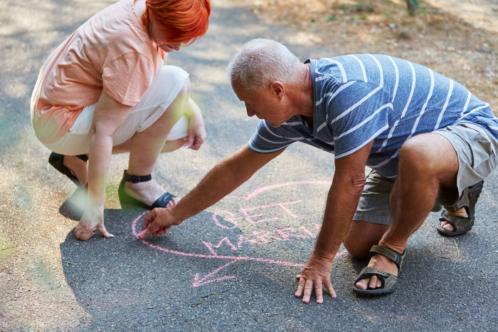 side view of two people Adult Boys Casual Clothing Chalk Child Childhood Couple Crouching Dating Dating Agency Dating Site Day Drawing Engagement Family Full Length Get Engaged Get Married Grandfather Happy Heart In Love Kneeling Leisure Activity Love Males  Man Marriage  Men Old Outdoors Outside Painting Partnership Pensioner People Retiree Romantic Senior Senior Adult Senior Citizens Senior Men Seniors Side View Son Symbol Together Togetherness Two People Wedding Woman