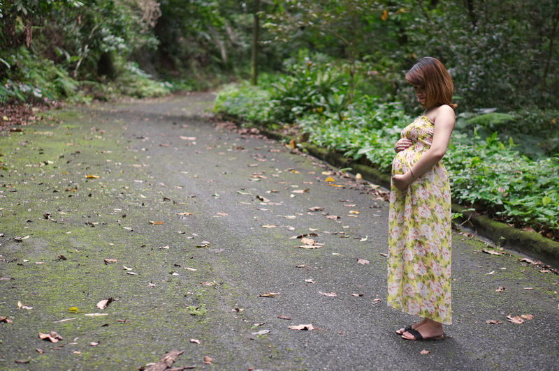 Full length of pregnant woman standing on road in forest