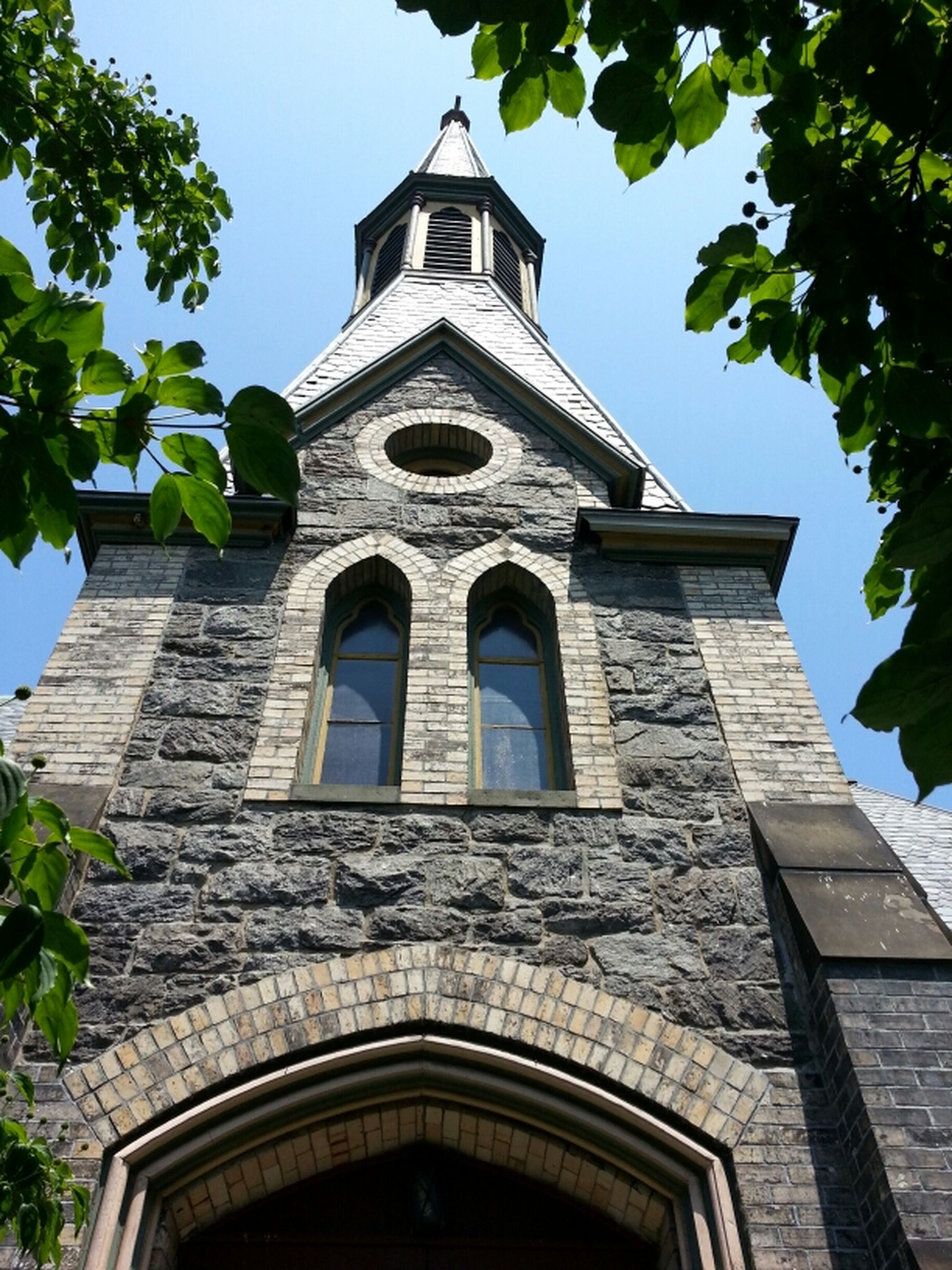 low angle view, architecture, building exterior, built structure, tree, religion, place of worship, sky, arch, church, history, window, day, no people, clear sky, outdoors, spirituality, facade, growth