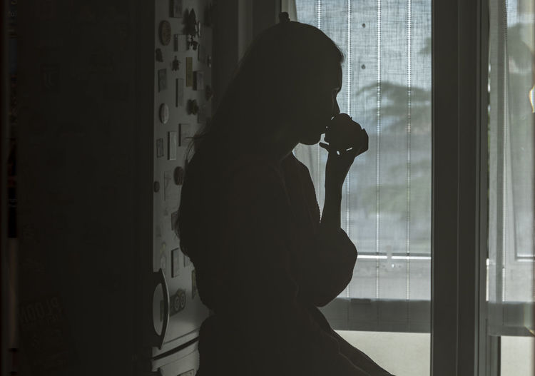 Silhouette woman looking through window at home