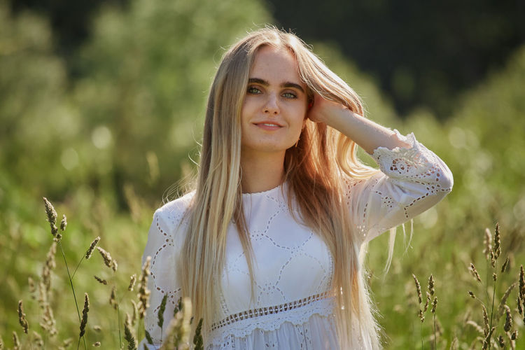 Portrait of beautiful young woman on field