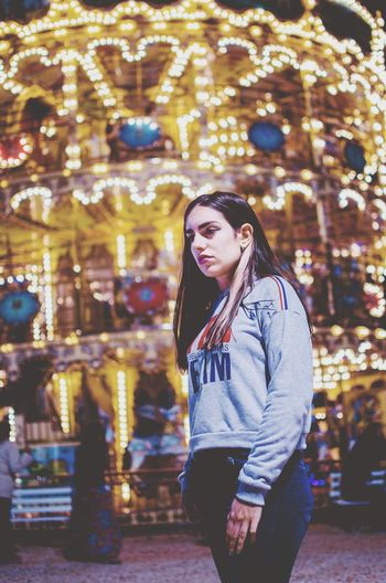 Young woman standing against illuminated amusement park ride
