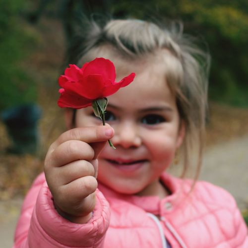 Close-up portrait of girl holding red flower