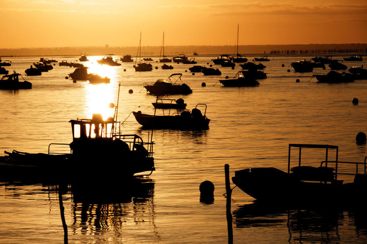 Boats In Calm Sea At Sunset