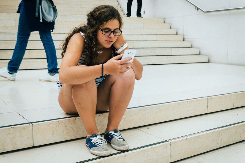 Teenage Girl Using Smart Phone While Sitting On Staircase
