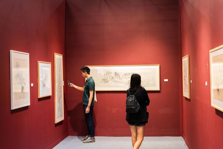 Rear view of people looking at corridor in museum