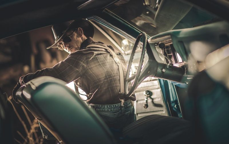 American Caucasian Cowboy Driver in His 30s Wearing Western Clothes and Sunglasses Seating Inside American Classic Muscle Car. American Countryside Theme. Classic Car Cowboy Wild West Car Indoors  Land Vehicle Men Mensfashion Mode Of Transportation Motor Vehicle Occupation People Real People Restro Seat Selective Focus Sitting Three Quarter Length Transportation Vehicle Interior Vintage Western Wear